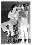 Male Sits on Stool as Female Holds Prop Up