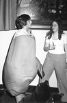 Female watches as male gets into strange puffy outfit by George Fox University Archives