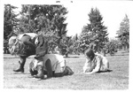 Three students play frog hop while in costume by George Fox University Archives