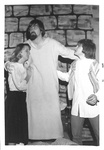 Female hugs taller male and other male puts arm on taller male's back by George Fox University Archives
