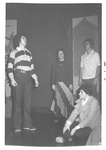 On stage, three students stand with arms straight down, one student sits to the side by George Fox University Archives