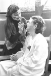 Female with face paint applies makeup on another students' face by George Fox University Archives