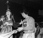 Two students in costume, one makes silly face, another grabs hands of person out of shot by George Fox University Archives