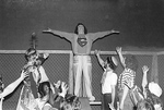 One student with superman shirt stands on bleacher with arms out to side, rest of students stand below and hold one arm up to student on bleacher