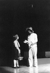 Man wears straw hat and talks with young boy