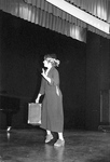 Female holds briefcase and waves on stage