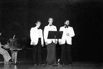 Three men in white suit jackets stand behind music stand and sing