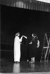 Woman in white robe holds out hand of a woman in black robe