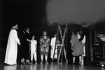 People in eclectic clothing stand around with a ladder in the middle