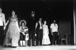 Actors and actresses stand in a row facing audience