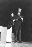 Woman and man with top hat stand and read a book