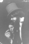 Close up of man in top hat next to woman in background