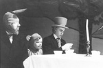 March Hare, Dormouse, and Mad Hatter sit at the end of the table