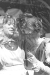 Actress holds face close to Alice's, who leans back