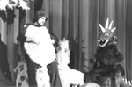 Actors in turtle and dinosaur costume sit near Alice by George Fox University Archives