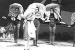 Alice stands in front of three actresses in flower costumes