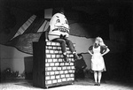 Humpty Dumpty sits on the brick wall while Alice looks up at him with hands on her hips