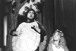 Man in turtle costume stands and talks next to Alice with finger pointing upward