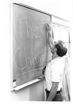 "Coach Rich Allen writes ""The Champs!"" on a chalkboard"