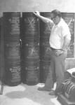 Bob Barnett rests hand on barrels of drinking water