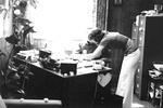 Judi Comfort stands at desk with Ron Crescelius