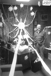 Ron Crecelius stands in office decorated with sun and flowers