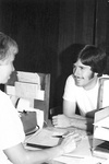 Katherine Eichenberger sits at desk with man