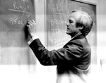 Don Millage writes numbers on a chalkboard by George Fox University Archives
