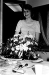 Staff member laughs behind flower bouquet by George Fox University Archives