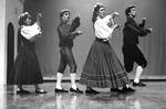 Four students perform dance on stage by George Fox University Archives