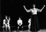 Female acts in front, other cast members sit on benches in back by George Fox University Archives