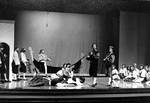 Cast members sit as two male actors perform musical piece in play by George Fox University Archives