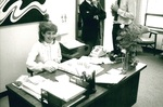 Susie McCarty sits at her desk by George Fox University Archives