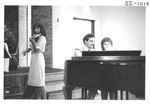 Couple Sitting at a Piano and Woman Playing the Violin by George Fox University Archives