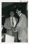 Man Greeting Someone While on Stage at an Alumni Reception by George Fox University Archives