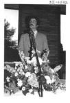 Man Speaking Behind a Podium at an Alumni Reception