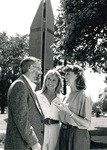 Three people enjoy conversation in front of the clock tower by George Fox University Archives
